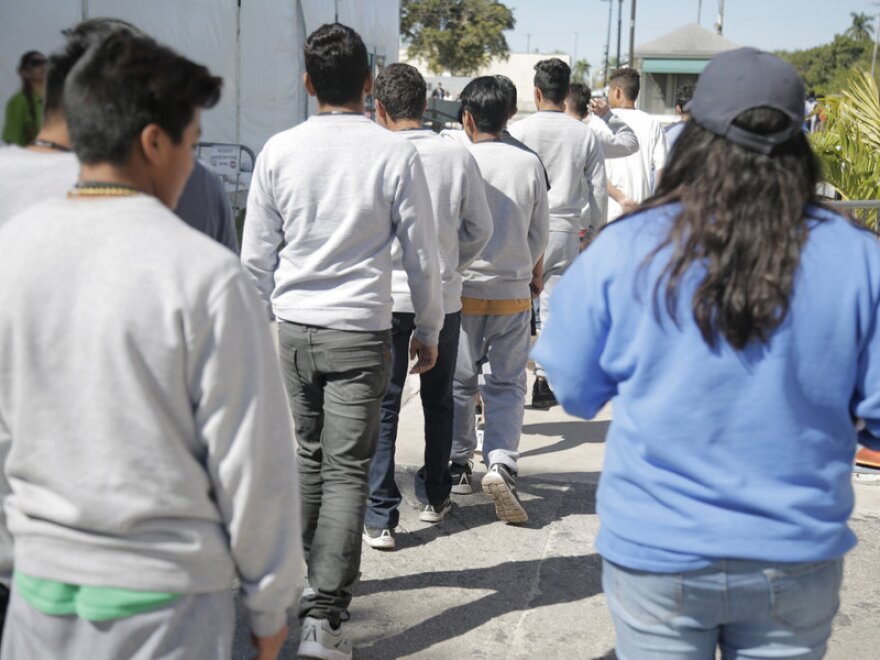 Migrant teens walking through the Homestead facility.