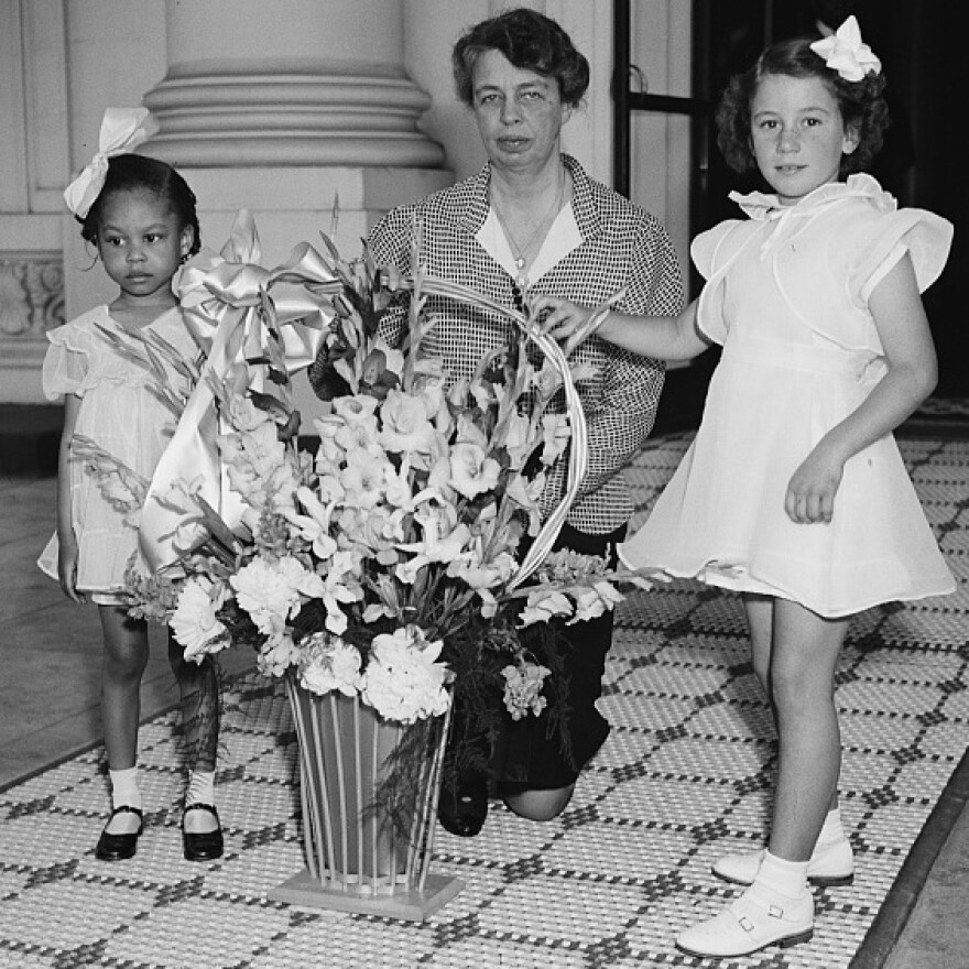 First lady Eleanor Roosevelt receives a May basket of flowers from young children in 1938.