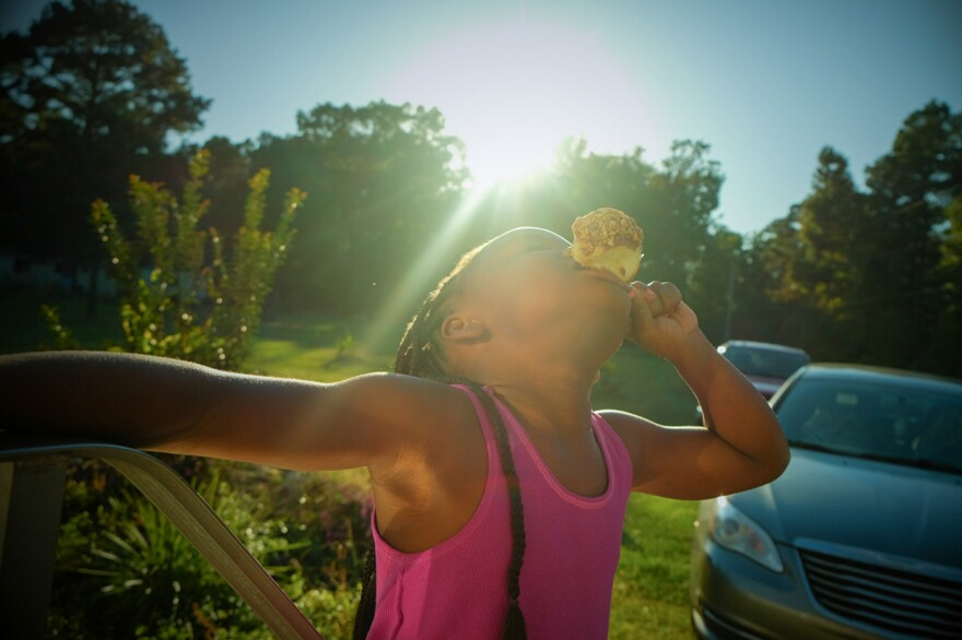 """The photographer's cousin Miyah eats a caramel apple days before Halloween. The picture is part of the series, """"Not Forgotten: An Arkansas Family Album."""""""