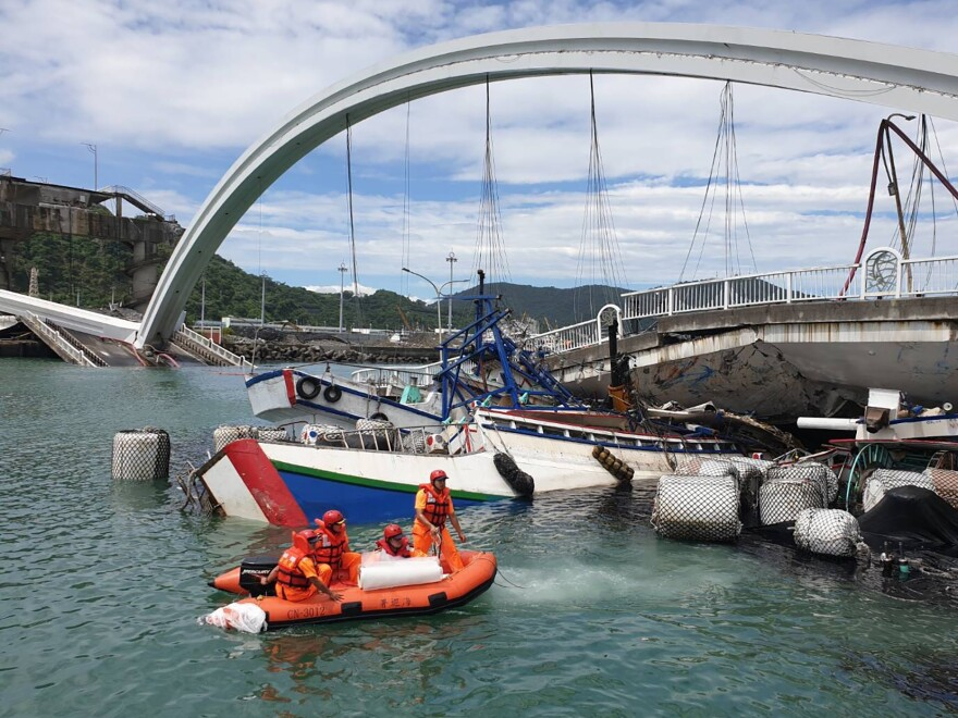 Rescuers work near the site of a collapsed bridge in northeastern Taiwan. On Tuesday, the towering Nanfangao Bridge collapsed, sending an oil tanker falling onto boats in the water below.