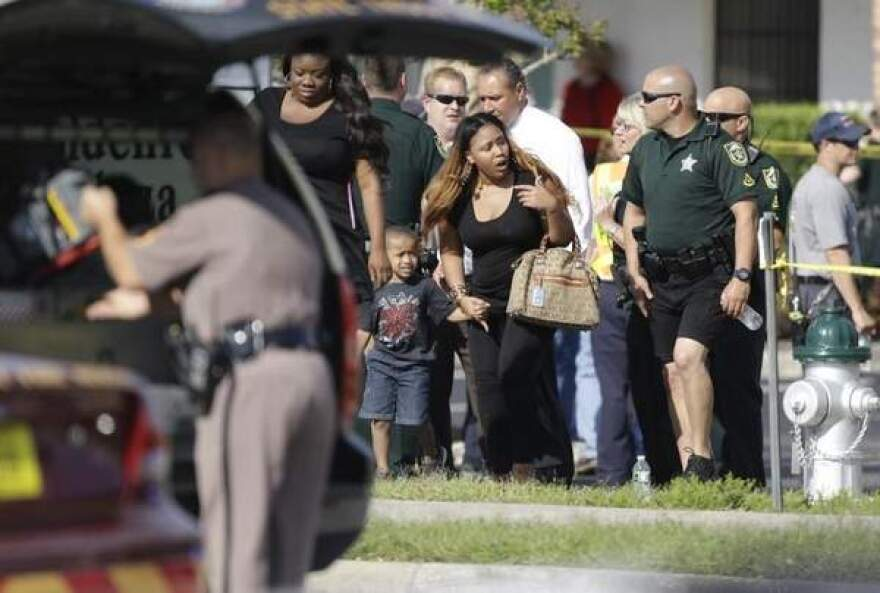 Parents with their children are escorted away with Orange County deputies after a vehicle crashed into a day care center Wednesday in Winter Park.