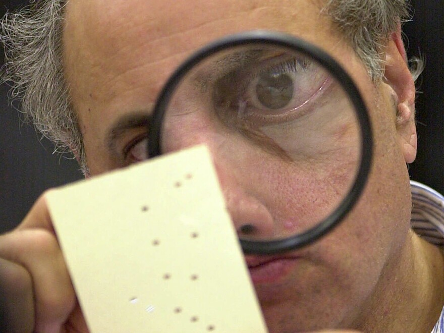 Judge Robert Rosenberg, a member of the Broward County, Fla., canvassing board examines a disputed ballot in Fort Lauderdale, Fla., on Nov. 24, 2000. That close presidential contest was one of several in U.S. history.