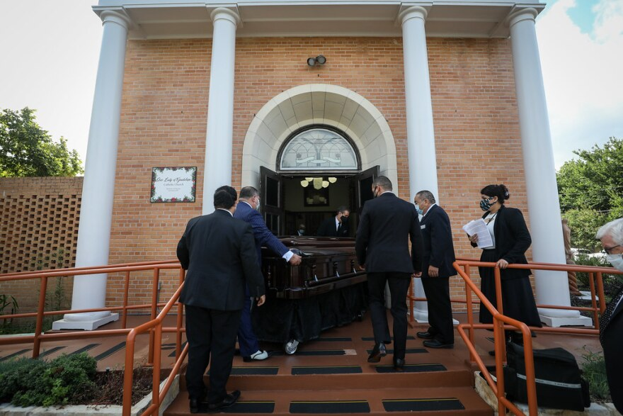 Pallbearers carry a casket holding the body of Lois Villaseñor inside of Our Lady of Guadalupe Parish.