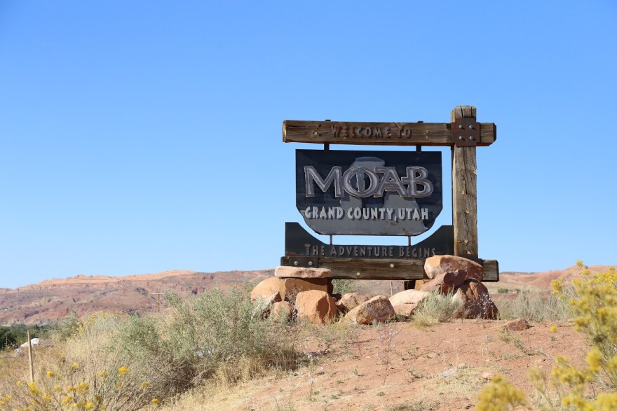 "A decorative road sign reads ""Welcome to Moab, Grand County, Utah."""