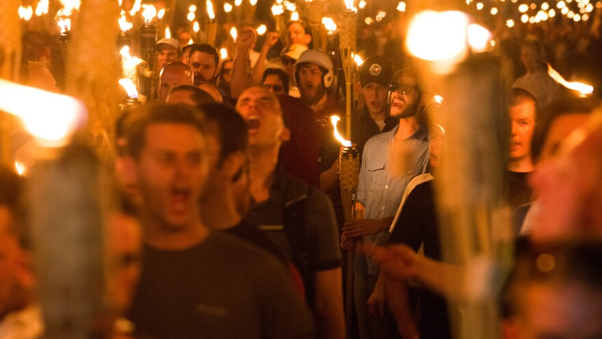 """White supremacists march through Charlottesville, Va., the night before the """"Unite the Right"""" rally in August 2017. Federal agents have arrested four men on riot charges connected to the rally."""