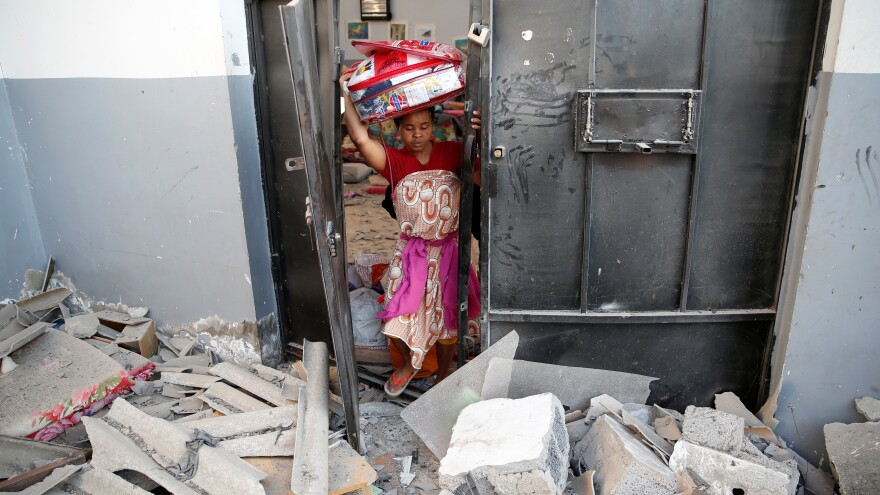 A woman picks up her belongings from among the rubble Wednesday, after an airstrike hit a detention center for mainly African migrants in the Tajoura suburb of Tripoli.
