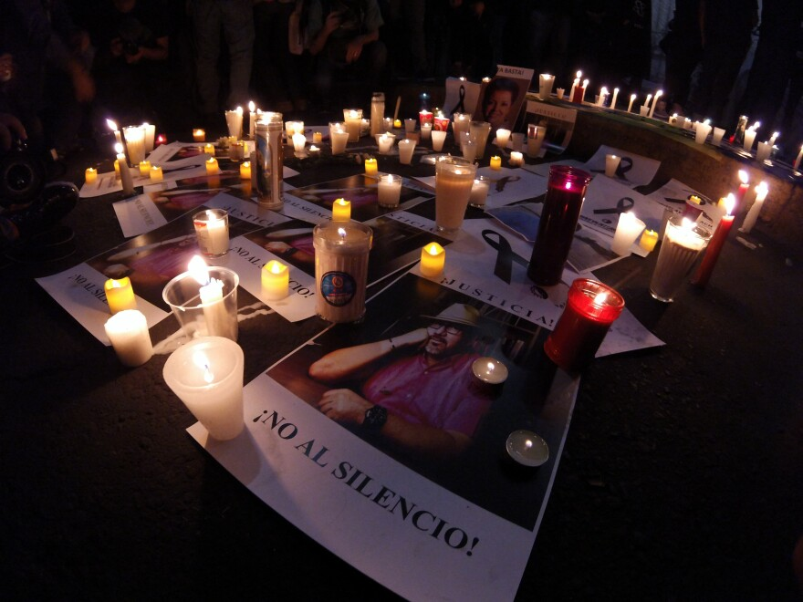 candles and flyers with image of slain Mexican journalist Javier Valdez