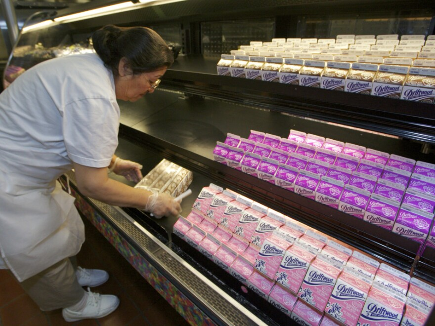 Belmont Senior High School cafeteria manager Carol Avalos stocked a refrigerated case with milk cartons in the Los Angeles school's cafeteria last month. The chocolate milk on the top shelf will soon be a thing of the past.