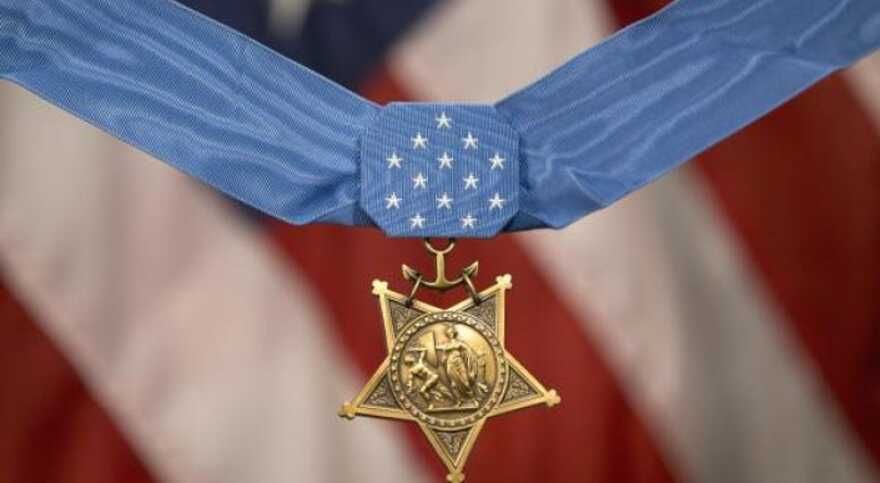 Close up of a medal of valor with an American flag in the background.