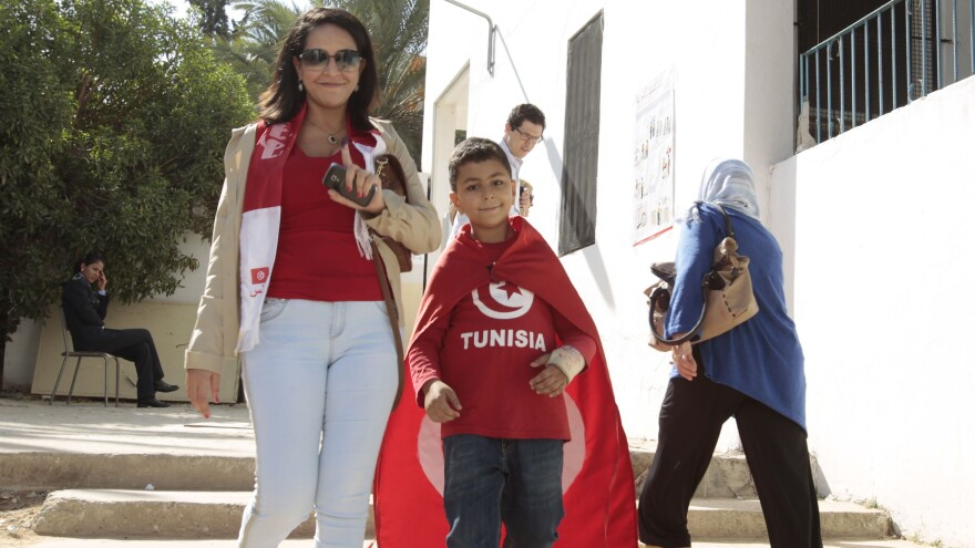 A voter raises her ink-stained finger after voting in Tunis Sunday. Tunisians voted in parliamentary elections that bring full democracy finally within their reach, in the cradle of the Arab Spring.