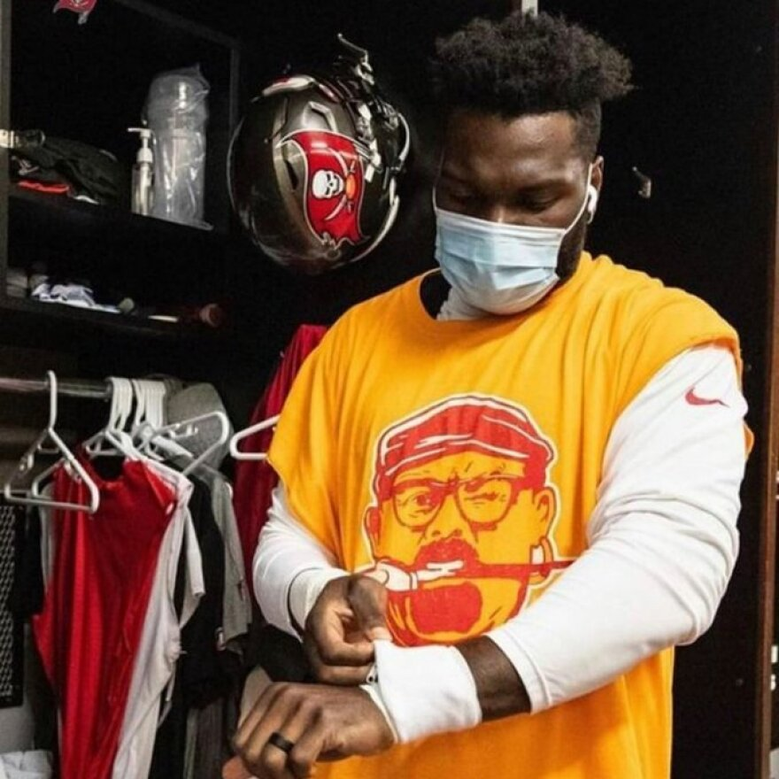 Football player wearing mask and t-shirt adjusts tape on his wrist