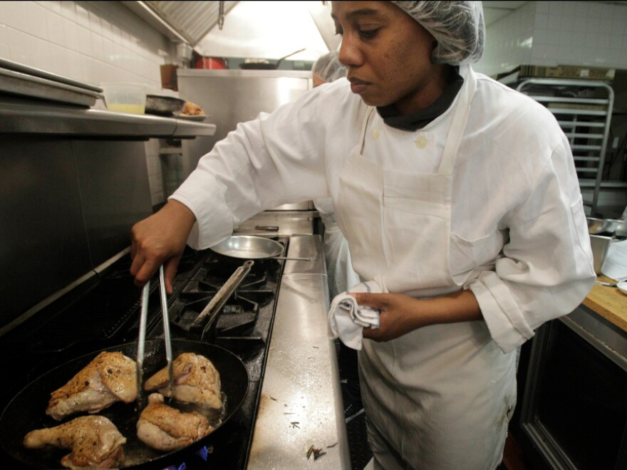 Culinary student Nadya Dunkley cooks chicken at Colors Restaurant in New York. The restaurant scored highly in a new guide that rates restaurants based on the way they treat employees.