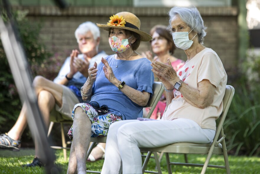 Neighbors listen to a free concert in the front yard of a Northwest Austin home on May 2.