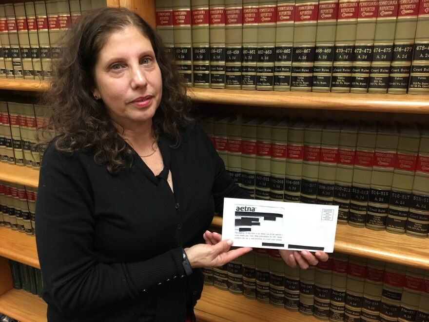 Ronda Goldfein, attorney and executive director of the AIDS Law Project of Pennsylvania, holds an envelope that revealed a person's HIV status through the clear window.
