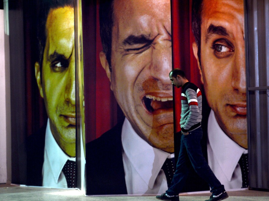 A man walks past posters of Egyptian satirist Bassem Youssef outside a theater in Cairo on Jan. 22.