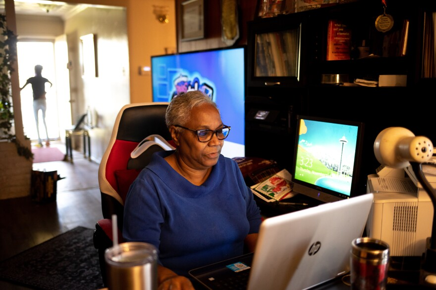 Marsha Jackson sits in front of her laptop in her living room while she works. Her granddaughter stands in the entrance of the house behind her.