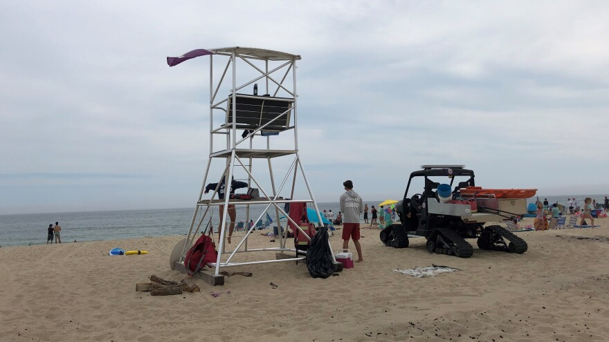 A taller lifeguard chair at Newcomb Hollow Beach is meant to help spot sharks and seals. Next to it, an all-terrain vehicle is equipped with a Stop the Bleed kit for shark bites.