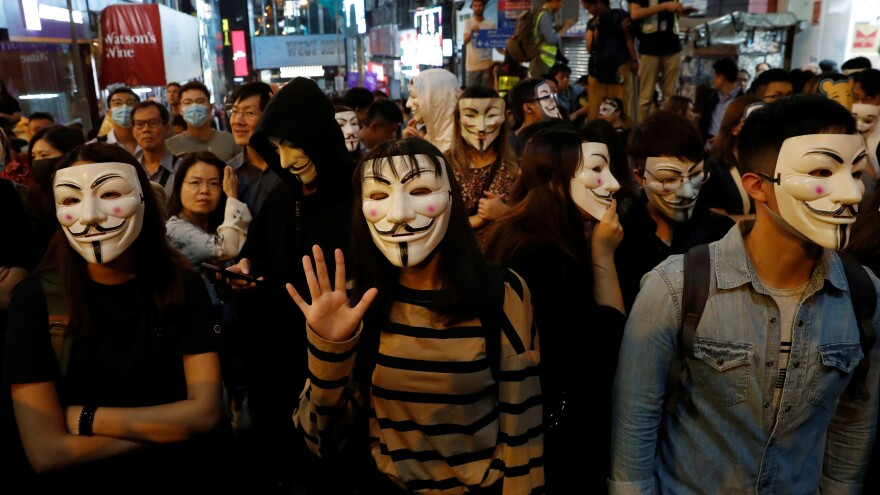 Anti-government protesters wear Guy Fawkes masks during Halloween in Hong Kong.