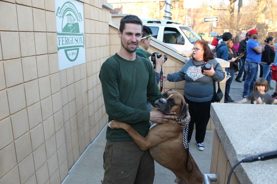 Ferguson resident Mike Arman hugs his dog Duke outside of Ferguson City Hall.