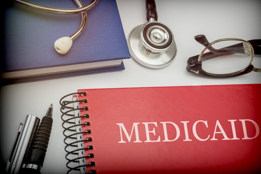 a red notebook on a desk with a pen, glasses and stethoscope.