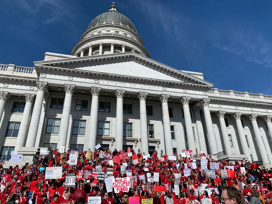 Photo of a crowd of people in red shirts holding signs advocating for public education funding in front of the utah state capitol building