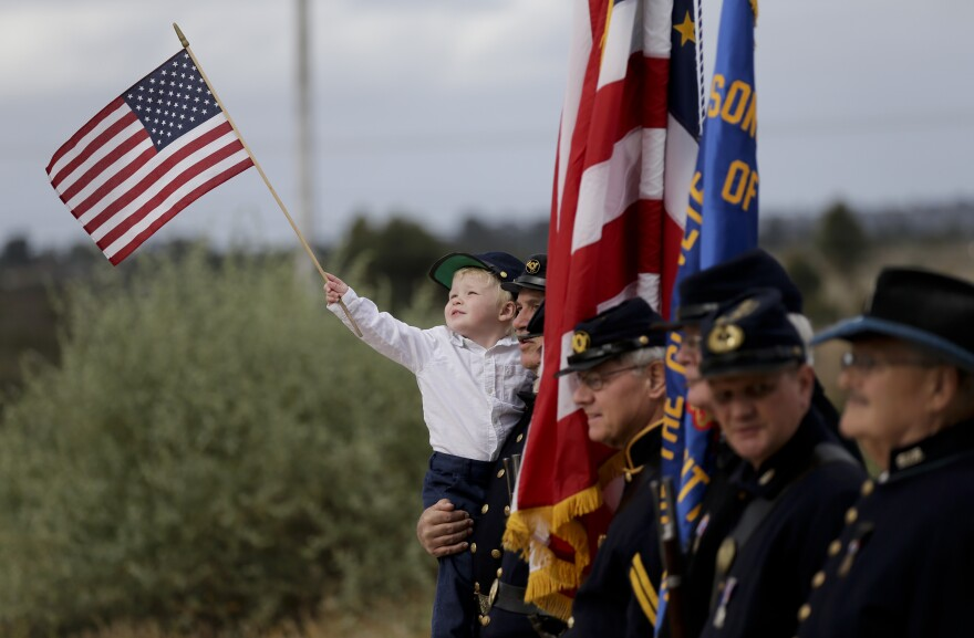 Stephen Tisch, 2, poses for a picture with Civil War re-enactors before Army Sgt. Charles Schroeter was re-interred at Miramar National Cemetery.