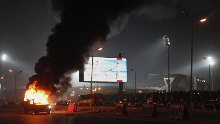 A pickup truck bursts into flames as a riot breaks out outside of a soccer match between Egyptian Premier League clubs Zamalek and ENPPI at Air Defense Stadium, in a suburb east of Cairo, on Sunday.