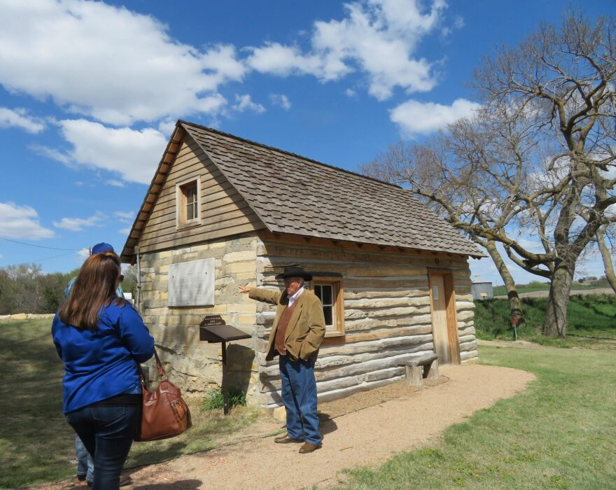 El Dean Holthus of Smith Center, Kansas, leads a tour of the property where Brewster Higley wrote 'Home on the Range,' including a restored cabin where Higley lived. (C.J. Janovy/KCUR)