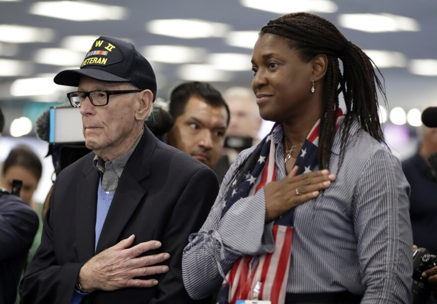 World War II veteran Sydney Levit, 94, of Aventura, Fla., left, stands with Paula Jarrett, of Honor Flight South Florida, during a sendoff celebration at Miami International Airport, Wednesday, May 22, 2019, in Miami. Levit is traveling to England where he will represent the United States as the guest of honor at the Memorial Day 75th anniversary ceremony at the Cambridge American Cemetery.