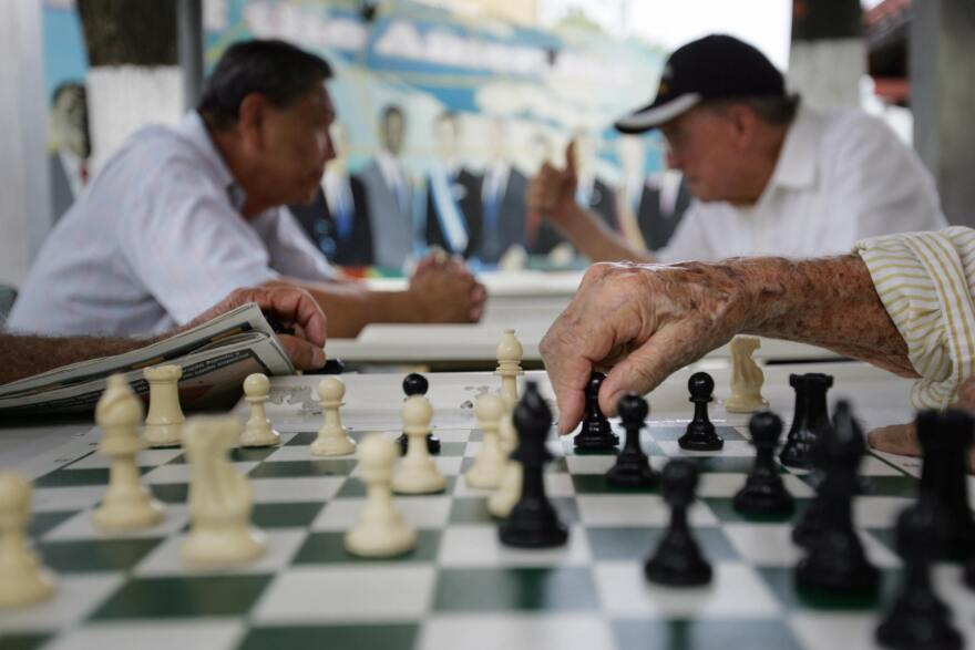 A elderly man makes a move on a chess board at the Maximo Gomez Domino park in Little Havana in Miami, where political opinions are shifting.