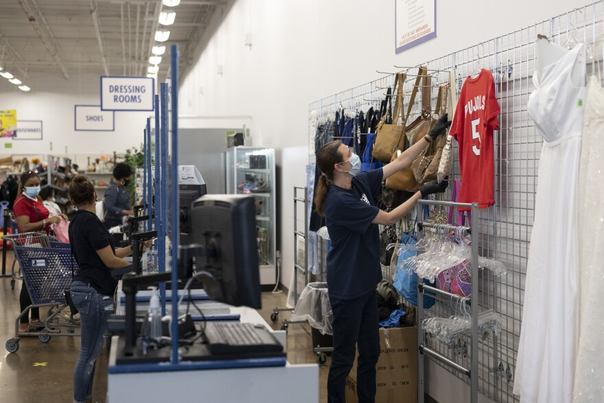 A cashier at MERS Goodwill retrieves a purse off a clothing rack at the thrift store chain's store in Manchester. Store employees wiped down carts between shoppers and halted sales of large furniture. May 18, 2020