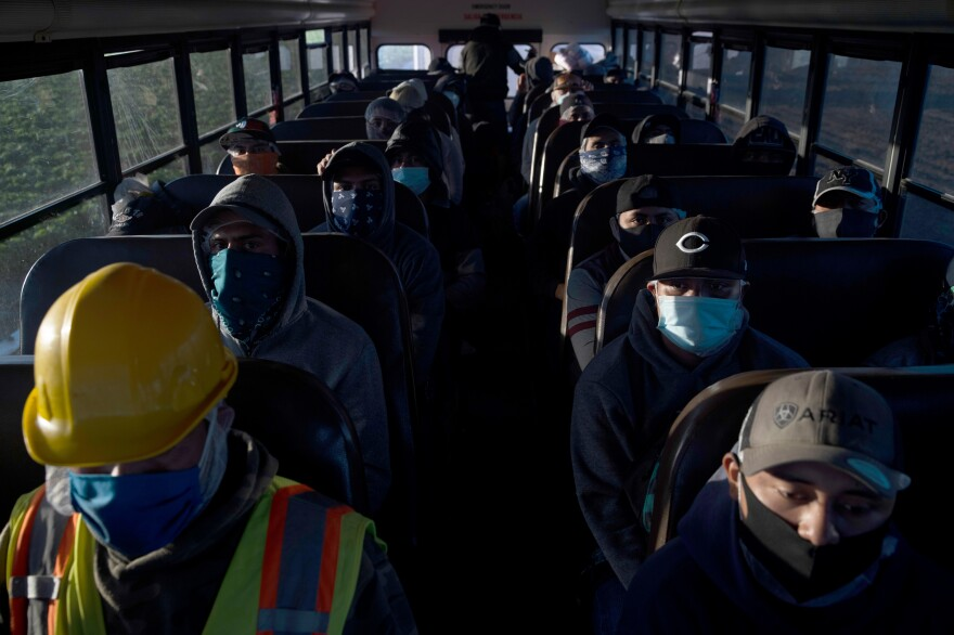 Farm laborers arrive for their shift in Greenfield, California, April 28, 2020. Traveling to the fields in crowded buses is one risk among others that workers often face daily.