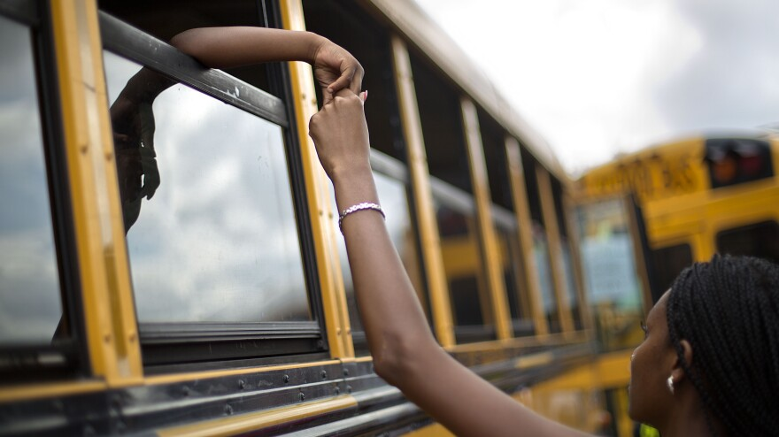 Laterrica Luther holds the hand of her 6-year-old nephew, Jaden Culpepper, as students from the Ronald E. McNair Discovery Learning Academy arrive on buses to waiting loved ones in a Walmart parking lot in Decatur, Ga., on Tuesday. A gunman had entered the students' school earlier in the day. No one was hurt.