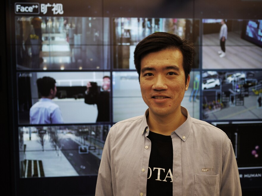 """Megvii Vice President Xie Yinan stands in front of several monitors exhibiting his company's facial recognition products. """"If a government is using it to control locals, we'd think twice about doing business with them,"""" he says. """"Our principle is to empower humans, not to control them."""""""