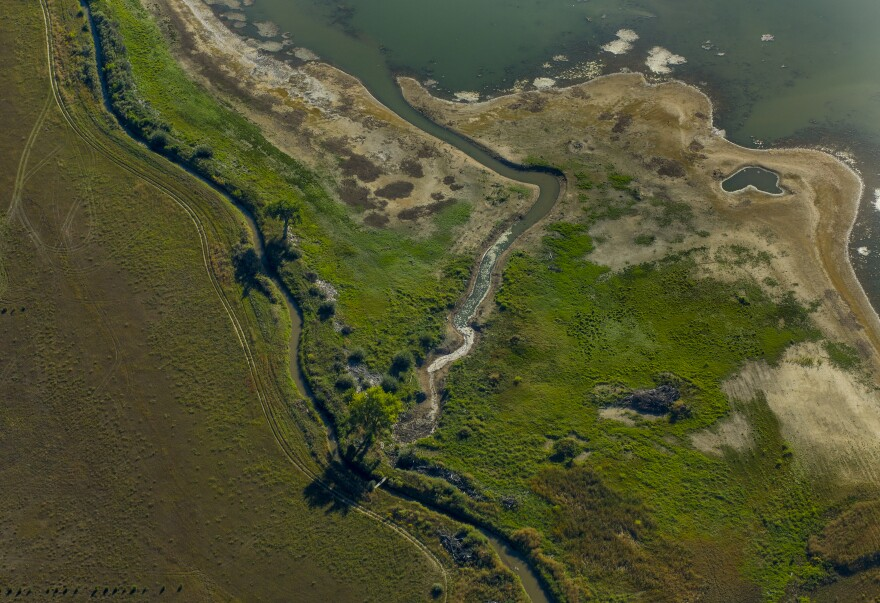 A ditch spills water into a storage pond on Colorado's Front Range.