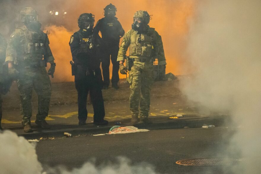Federal police walk through tear gas while dispersing a crowd of about a thousand protesters at the Mark O. Hatfield U.S. Courthouse in Portland, Ore.