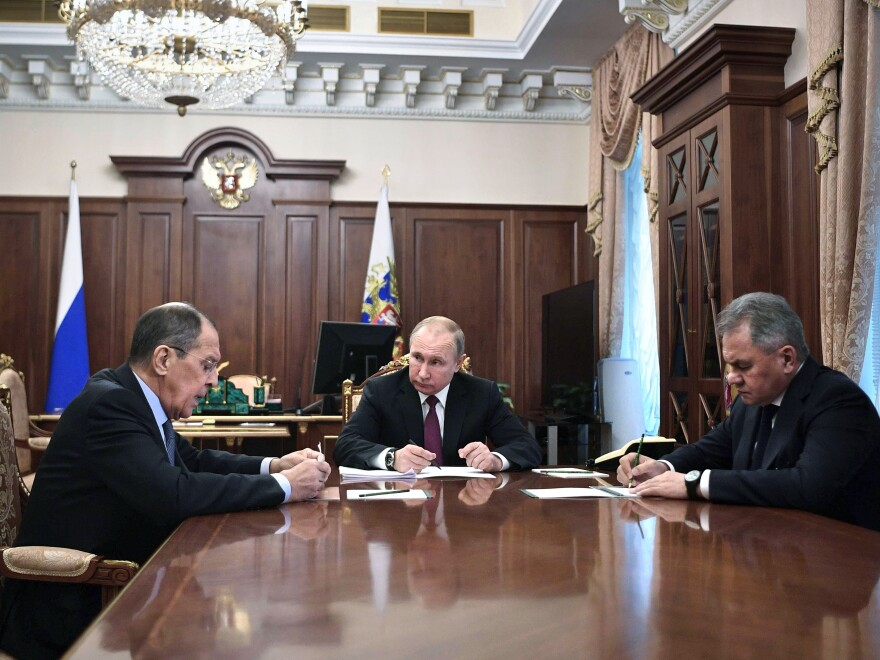 """Russian President Vladimir Putin (center) attends a meeting with Russian Foreign Minister Sergey Lavrov (left) and Defense Minister Sergei Shoigu in the Kremlin in Moscow on Saturday. Putin said Russia would abandon the 1987 Intermediate-Range Nuclear Forces treaty, calling it a """"symmetrical"""" response to the U.S. decision to withdraw."""