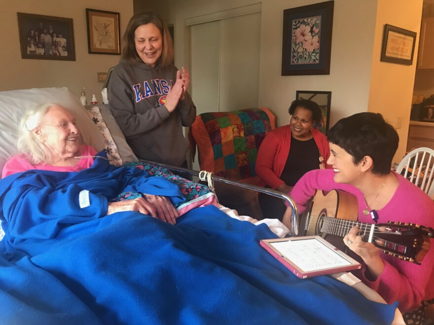 Hospice patient Dorothy Matejka enjoys a music therapy session with her daughter Nancy Daake and music therapists Alison Cole and Kathryn Coccia, seen here with her guitar.