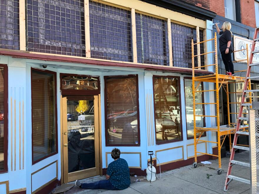 Melissa Martin stands on top of scaffolding to paint the top trim of her new storefront in Chillicothe.