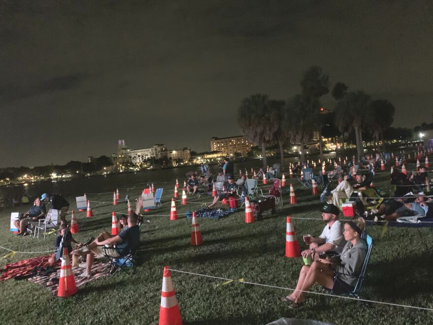 Fans sit in socially-distanced sections of a lawn near the St. Pete Pier for a Rays watch party.