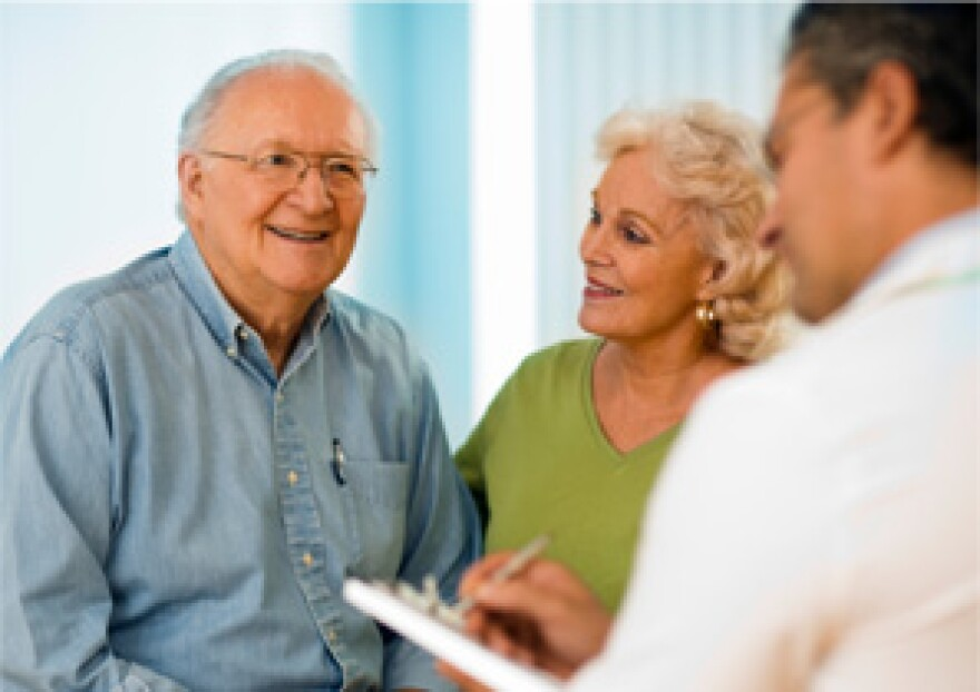 Doctor providing information to an elderly couple.