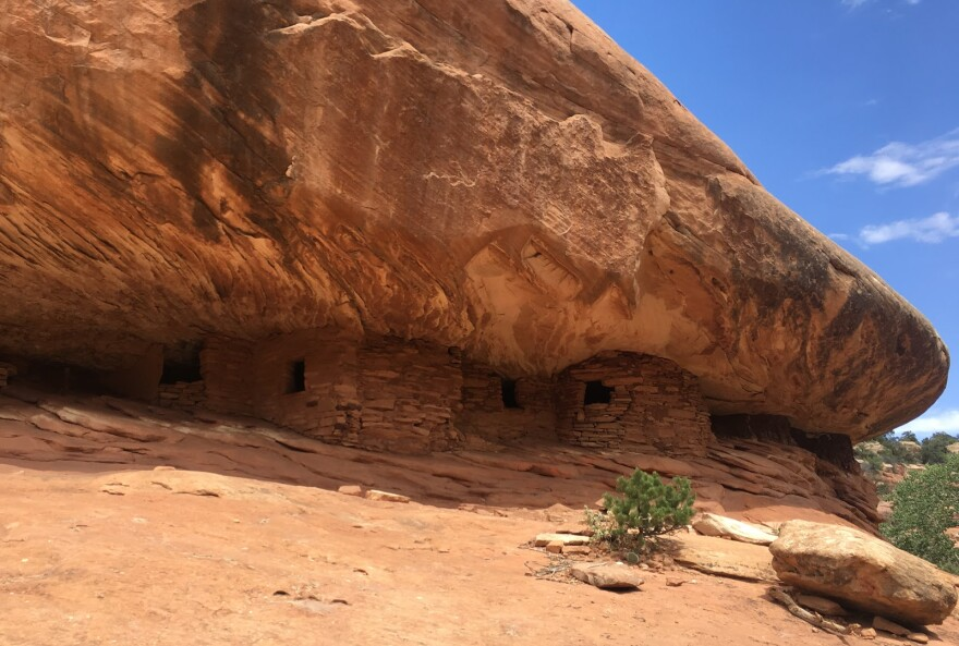 an ancient stone structure nestled inside a red rock cliff