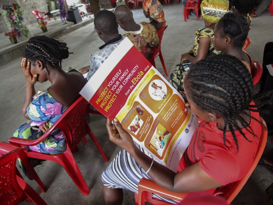 A woman reads a poster on the prevention of Ebola at a UNICEF event in Monrovia, Liberia, on June 22.