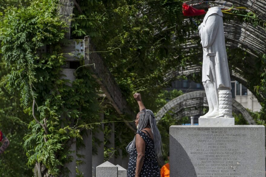 A woman poses in front of a decapitated statue of Christopher Columbus viewed at Christopher Columbus Park in Boston Massachusetts on June 10, 2020.