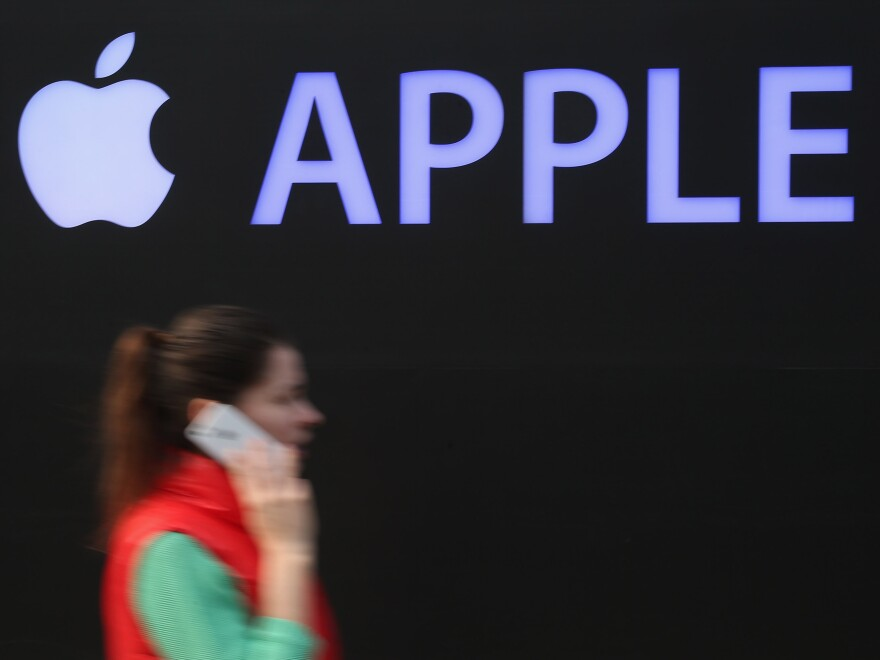 A woman talks on an iPhone as she walks past construction of a new Apple store in Berlin in April.