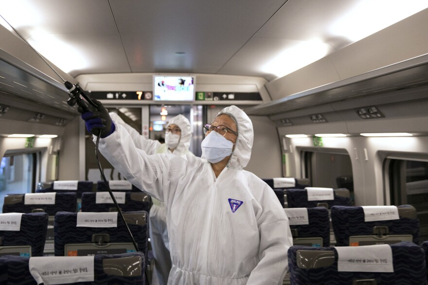 Workers spray disinfectant in a train as part of efforts to prevent the spread of a new virus which originated in the Chinese city of Wuhan at Suseo railway station in Seoul, South Korea on January 24, 2020.