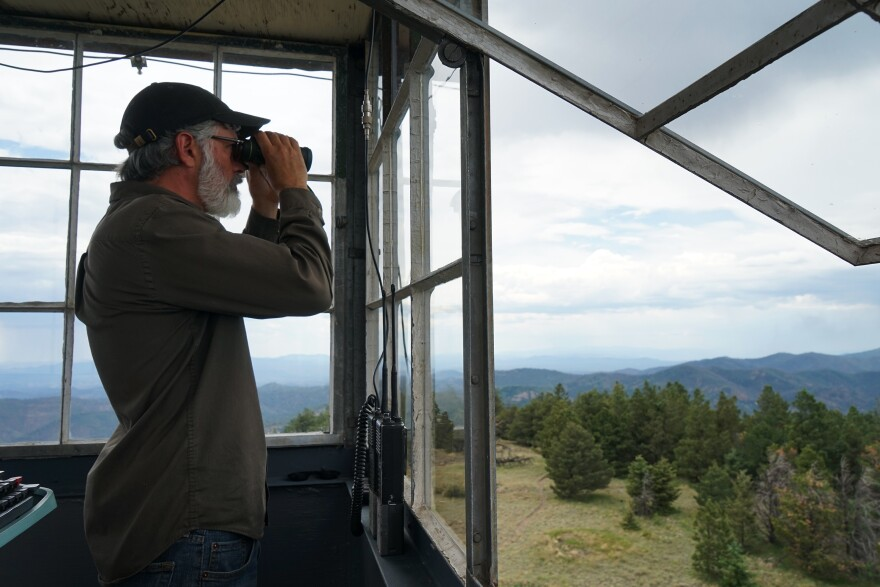 Connors looks through his binoculars. He's spent thousands of hours contemplating the contours of southwest New Mexico.