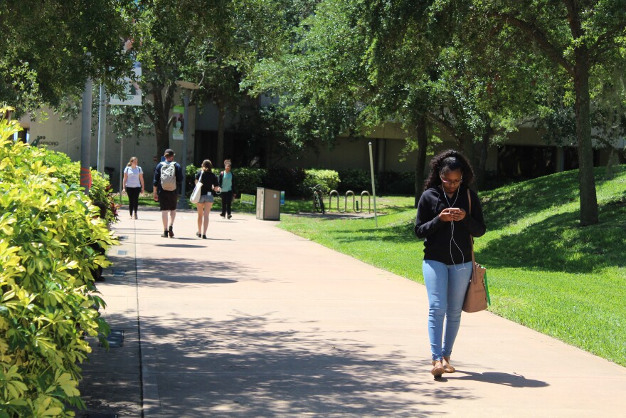student walking on campus, looking at her phone