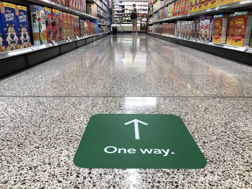 A close up of the one way aisle sticker at publix with a woman wearing a mask in the background.