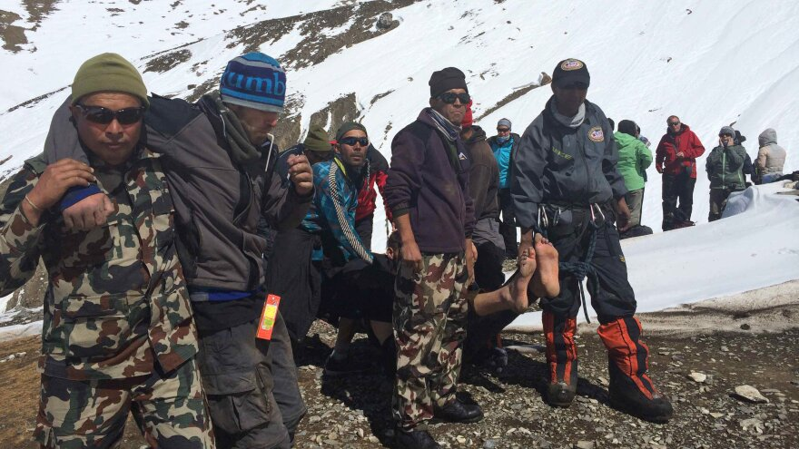 In this photo dated Oct. 17, rescue team members carry avalanche victims to safety at Thorong La pass in Nepal.